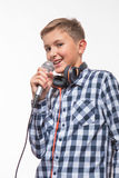 Garçon blond de chanteur émotif dans une chemise de plaid avec un microphone et des écouteurs Photo libre de droits