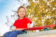Garçon blond de sourire s'asseyant avec la planche à roulettes Image libre de droits