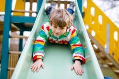 Garçon blond heureux d'enfant ayant l'amusement et glissant sur le terrain de jeu extérieur Photos libres de droits