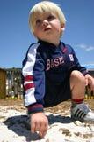 Garçon blond jouant dans la cour de jeu arénacée Image stock
