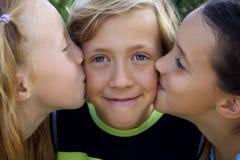 Garçon blond mignon embrassé par deux filles photo libre de droits