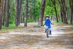 Garçon blond mignon heureux d'enfant ayant l'amusement son premier vélo le jour ensoleillé d'été, dehors enfant faisant des sport Photos libres de droits