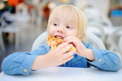 Garçon blond mignon mangeant la tranche de pizza au restaurant d'aliments de préparation rapide Image libre de droits
