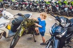 Garçon blond mignon regardant motocyclette de denrées de moto de vintage la nouvelle photos libres de droits