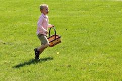Garçon blond mignon sur une chasse à oeuf de pâques Image stock