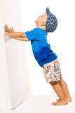 Garçon blond poussant il murent le bacground blanc Photographie stock libre de droits