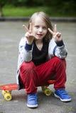 Garçon blond s'asseyant sur la planche à roulettes et faisant le signe de paix Images libres de droits