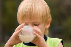 Garçon buvant sur le lait de nature Photo libre de droits