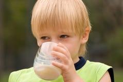 Garçon buvant sur le lait de nature Photo stock