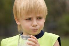 Garçon buvant sur le lait de nature Image stock