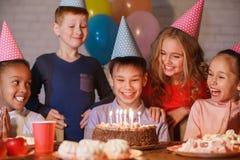 Garçon célébrant l'anniversaire et faisant le souhait à la maison photographie stock libre de droits