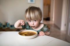 Garçon caucasien adorable d'enfant en bas âge mangeant de la soupe saine dans le kitch Photos stock