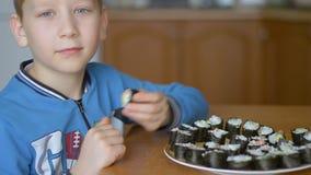 Garçon caucasien mangeant des petits pains à la maison dans la cuisine clips vidéos