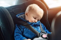 Garçon caucasien mignon d'enfant en bas âge dormant au siège de sécurité pour enfants dans la voiture pendant le voyage par la ro image libre de droits