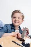 Garçon caucasien pratiquant pour jouer sur la guitare d'isolement sur le blanc photos stock