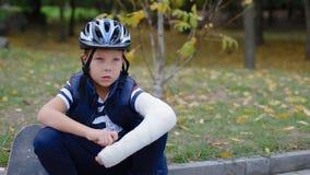 Garçon caucasien s'asseyant à la frontière avec son patin clips vidéos