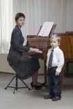 Garçon chantant comme professeur Play The Piano Photo libre de droits
