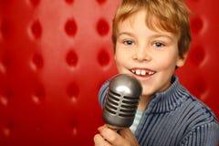 Garçon chanteur avec le microphone sur l'armoire contre le rouge Images libres de droits