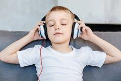 Garçon charismatique d'une manière amusante écoutant de la musique Photographie stock libre de droits