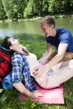Garçon chatouillant la fille par le lac Photographie stock