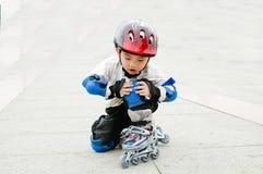 Garçon chinois jouant le patin images stock