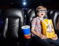 Garçon choqué observant le film 3D dans le théâtre Photo stock