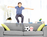 Garçon comblé sautant sur le divan à la maison Photographie stock