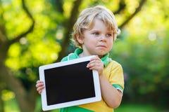 Garçon confus adorable de petit enfant tenant le PC de comprimé, dehors Photographie stock libre de droits