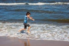 Garçon courant sur une plage image libre de droits