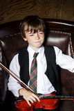 Garçon couvert de taches de rousseur de rouge-cheveux avec le violon se reposant dans le fauteuil Images stock