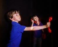 Garçon couvert de taches de rousseur parlant le téléphone rouge à l'ancienne, double-exposition Photos stock