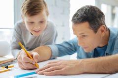 Garçon curieux observant son père dessiner un modèle Images stock