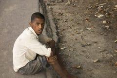 Garçon désespéré de profil d'autisme pauvre s'asseyant dans la route Photo stock