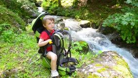 Garçon détendant dans un transporteur d'enfant près de la rivière banque de vidéos