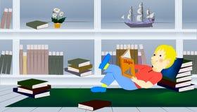 Garçon détendant sur le plancher lisant un livre image stock