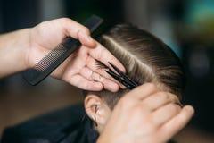 garçon d'Little atteignant la coupe de cheveux par Barber While Sitting In Chair le raseur-coiffeur  photographie stock