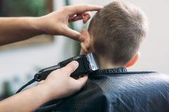 garçon d'Little atteignant la coupe de cheveux par Barber While Sitting In Chair le raseur-coiffeur  images libres de droits