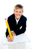 Garçon d'école avec du charme écrivant son affectation images stock