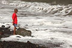 Garçon d'école ethnique sur la plage observant la vague déferlante Photo libre de droits