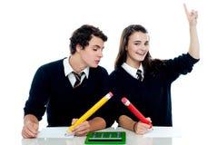 Garçon d'école piaulant dans la formule d'utilisation de filles Photos stock