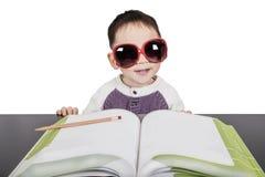 Garçon d'écolier dans le livre d'étude en verre Image libre de droits