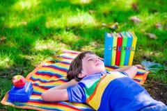 Garçon d'étudiant détendant dans des livres de lecture de cour d'école Images stock