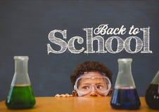 Garçon d'étudiant se cachant derrière une table contre le tableau noir bleu avec de nouveau au texte d'école Photographie stock libre de droits