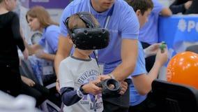 Garçon d'adolescent à l'aide du casque de réalité virtuelle à l'exposition de technologie banque de vidéos