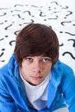 Garçon d'adolescent avec des questions Photos stock