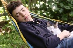 Garçon d'adolescent avec le chat dans le petit somme de monticule Images libres de droits