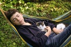 Garçon d'adolescent avec le chat dans le petit somme de monticule Images stock