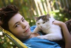 Garçon d'adolescent avec le chat dans le petit somme de monticule Image stock