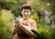 Garçon d'adolescent avec le chat dans le petit somme de monticule Photo libre de droits
