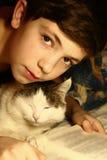 Garçon d'adolescent avec le livre de lecture de chat Photo stock
